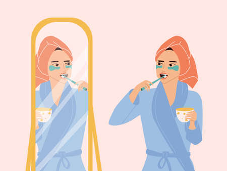 A cute girl in a turban and a dressing gown stands at the mirror and brushes her teeth, holds a mug in her hands. Daily morning routine, care for teeth and beauty. Colorful vector flat illustration. 向量圖像