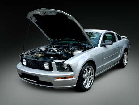 クリッピング パスと黒の背景上に分離されてオープン フード付き銀白色の筋肉の車