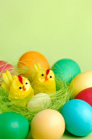 Colorful Easter eggs and two decorative chicks in a nest Artistic still life isolated on light green background Stock Photo