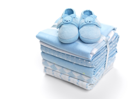 Cute blue baby boy shoes on a pile of swaddling blankets isolated on white background