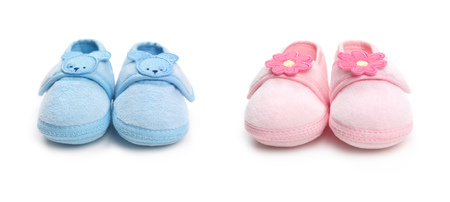 Closeup of cute pink and blue baby boy and girl shoes isolated on white background