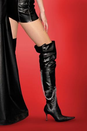 61eb81b6cdf22 Foto de archivo - Mujer atractiva en traje de cuero y de cuero negro botas  altas de tacón de aguja