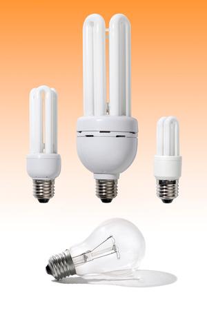 Three energy-efficient light bulbs of different power 5, 15 and 40 Watt above a regular 120 Watt light bulb Power saving economy electricity moder technologies concept Reklamní fotografie