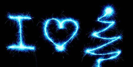 I Love Christmas, heart shape and a Christmas tree made with a sparkler light on black background
