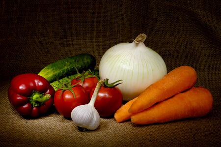 Light-painted colorful vegetable country-style still life with tomatoes, onion, bell pepper, cucumbers, carrots and garlic on sacking fabric background Фото со стока
