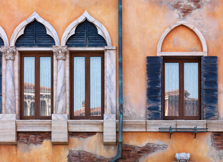 Yellow wall of antique Venetian building with old arched windows, rustic texture Banco de Imagens