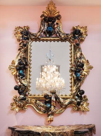 Decorative golden renaissance period mirror frame on a wall Standard-Bild