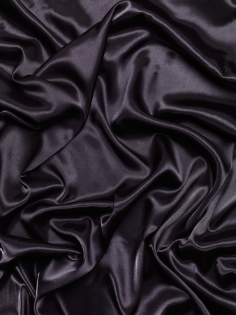 Black shiny silky fabric abstract folds background texture