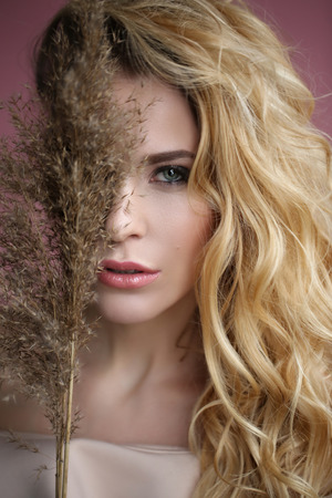 Portrait of a blonde in the dress with a plant Stock Photo