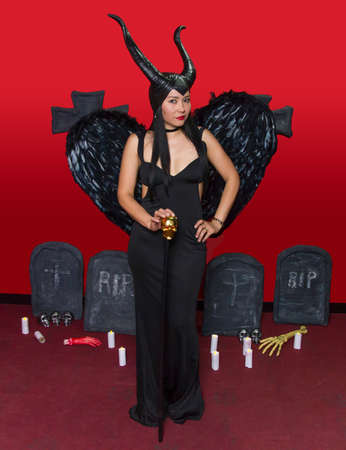 Beautiful girl dressed as maleficent in red background with horns and wings Stock Photo