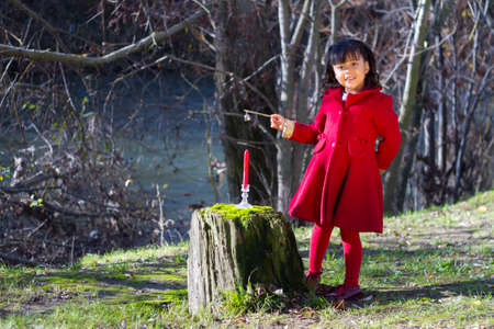 Little girl in red dress playing at Christmas and with autumn leaves