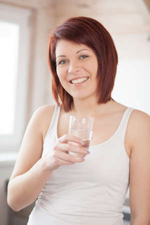 Young Woman in Kitchen with Glas Water photo