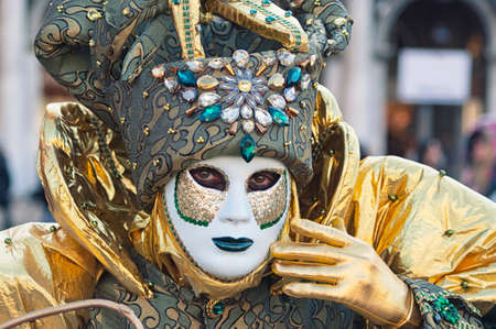 Portrait of a man wearing a white and green mask during the Venetian carnival party in San Marco square Editorial