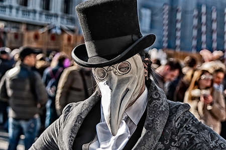 Portrait of a woman wearing mask of a plague doctor during the Venetian carnival party in San Marco square