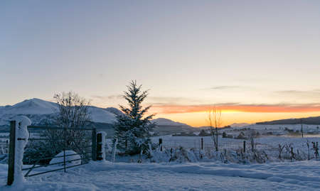Beautiful sunset on a scottish valley covered in snow in the Highlands with mountains in the background and a clear sky ideal for copyspace