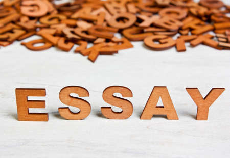 essay: Word Essay made with wooden letters on a background of other blurred letters
