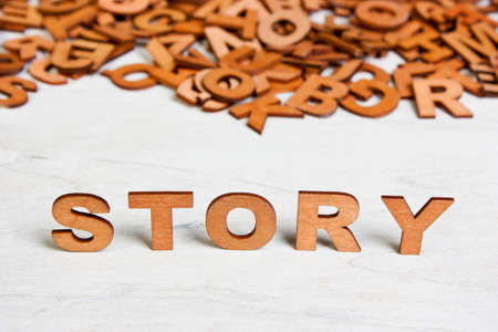 bookish: Word Story made with wooden letters on a background of other blurred letters Stock Photo
