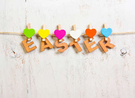 clothespins: Easter word made of wooden letters with colored hearts clothespins on a white background old Stock Photo