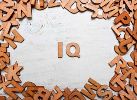 iq: Word IQ (intelligence quotient) are made with wooden letters on an old white wooden background