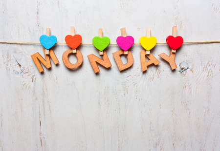word Monday from wooden letters with colored clothespins on a white wooden background