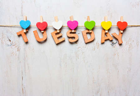word Tuesday from wooden letters with colored clothespins on a white wooden background Stock Photo