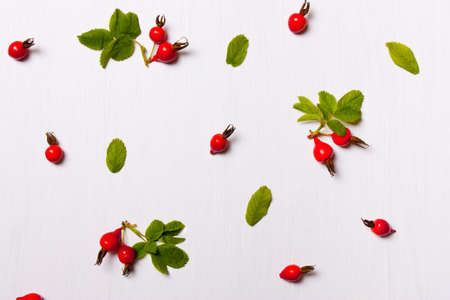 The pattern, composition of rose hips, berries and leaves on a white background. Flat lay, overhead view