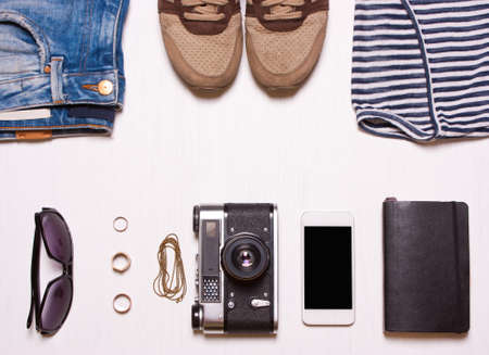 collaget, set hipster womens clothing, accessorieson.rings, glasses, camera, phone, notebook, shoes, sneakers a white background.Concept fashion person, hipster, photographer