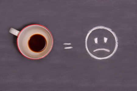 A cup of coffee and sad smiley drawn with chalk on the table. Energy from coffee.