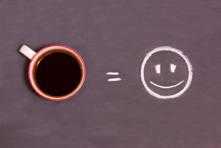 A cup of coffee and smiling smiley drawn with chalk on the table. The concept of a good morning. Energy from coffee.