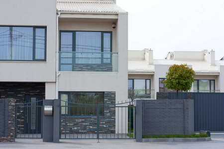 cottage fence: Cottage house behind the fence. Modern exterior of home.Modern stylish facade