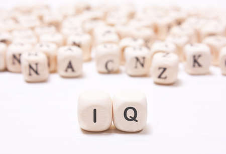 iq: The word IQ on the white  dice on a background of blurred letters. The concept of the mind, the intellect Stock Photo