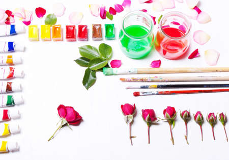 flat brushes: Workplace artist, designer. Paints, brushes, flowers and roses. Concept art and inspiration. Top view, flat