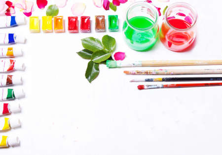 flat brushes: Workplace artist, designer. Paints, brushes, flowers and roses. Concept art. Top view, flat