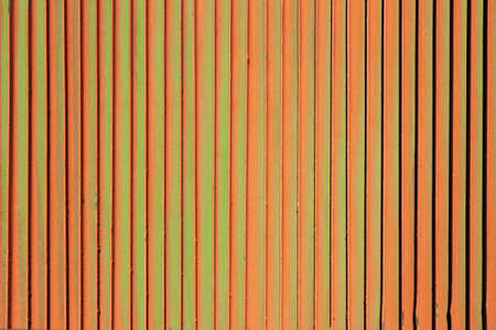 oxidate: Orange rusty green background. Corrosion of metal iron. Vertical fence