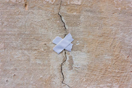 wall with a crack and a patch. Concept of repair, restoration, unification Foto de archivo - 104917529