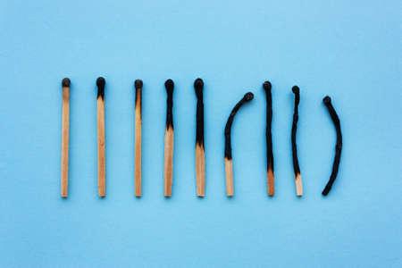 Fiammiferi bruciati in fila su sfondo blu. Il concetto di depressione, estinzione, malattia, burnout, invecchiamento. Vista dall'alto, piatta