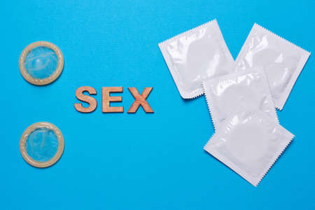 Condom and word sex on a blue background. Flat view, from above.