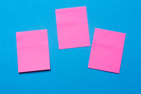Three empty pink notes, a sticker on a blue background for writing ideas and tasks