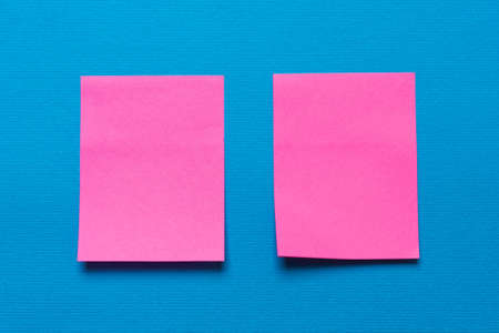 Two empty pink notes, a sticker on a blue background for writing ideas and tasks