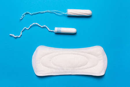 Women's hygiene products, pad, tampon on a blue background. Concept of critical days, menstrual cycle, menstruation 版權商用圖片 - 107867920