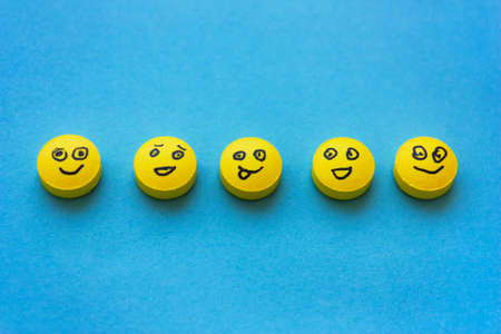 Yellow pills with smiles on a blue background. The concept of treatment, positive, depression