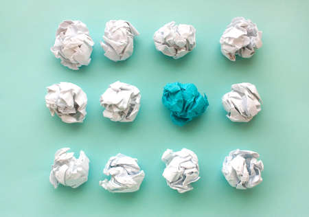 blue wrinkled ball of paper among the whites. Concept of ideas, differences, leadership. View from above, flat