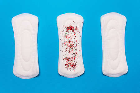 three menstrual pads on a blue background. Concept of critical days, menstrual cycle, menstruation Stock Photo