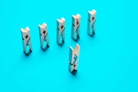 Wooden clothespins on a blue background. Leadership concept, creativity.Soft focus Stock Photo