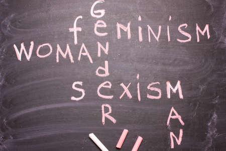 Words gender, sexism, feminism written in pink chalk on a chalkboard