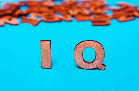 Word ,abbreviation IQ of wooden letters on a blue background Stock Photo