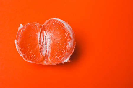 Concept sex, masturbation. Grapefruit, vagina symbol on orange background