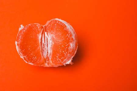 Konzept Sex, Masturbation. Grapefruit, Symbol auf orangem Hintergrund