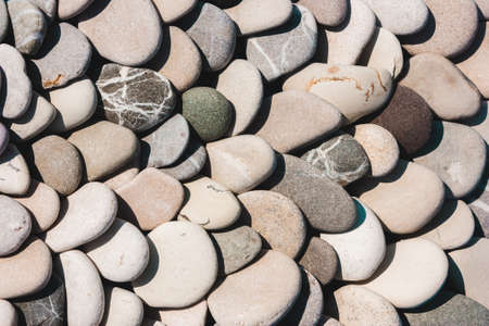 Marine naturally rounded gravel, pebbles in a row. Nature Background Texture Stock Photo