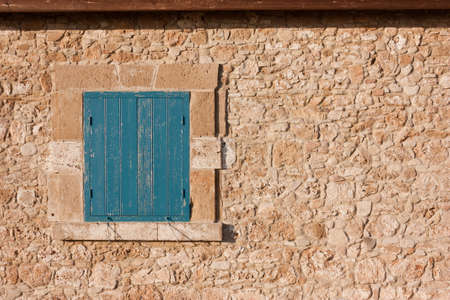 Antique wall of stone and blue wooden shutters on the window. Traditional vintage walnut, cypriot european style Stock Photo